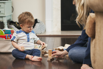 Mother and little son playing with building blocks