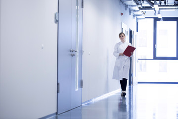 Young woman in lab coat walking on floor holding folder