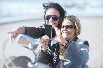 Two women on motorcycle taking selfie