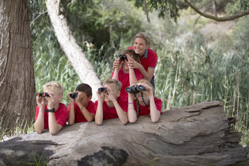 South Africa, Kids on field trip exploring nature, looking through binoculars