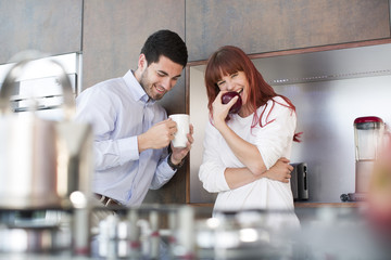 Happy couple in kitchen with apple and cup of coffee