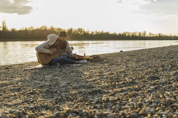 Couple at the riverside playing guitar