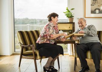 Senior couple watching photo album at home