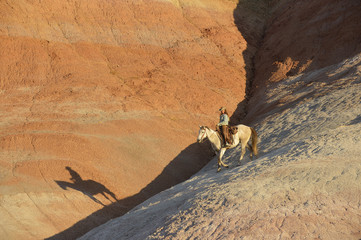 USA, Wyoming, cowgirl riding in badlands at twilight