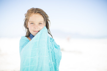 Smiling girl on beach wrapped in a towel
