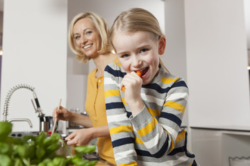 Mother with daughter eating carrot in kitchen