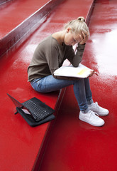 Female teenager with booklet and laptop reading on red stairs