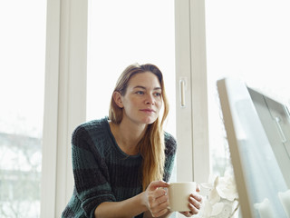 Young woman sitting at window, holding cup of coffee