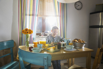 Boy sitting at breakfast table using smartphone
