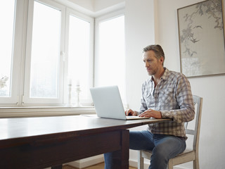 Germany, Cologne, Mature man at home using laptop