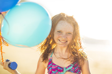Girl on the beach smiling and holding balloons