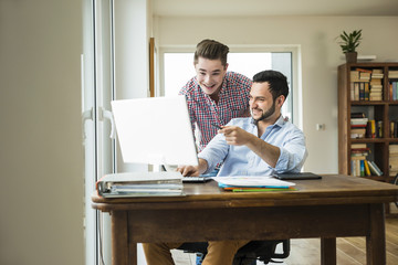Two smiling young men looking at computer monitor