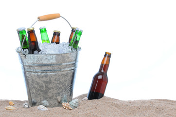 Assorted beer bottles in a bucket of ice in the sand