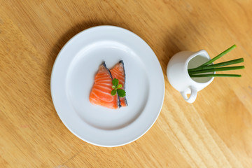 salmon in white dish on wooden