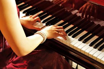 グランドピアノを弾く女性の手