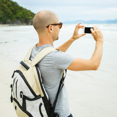 Handsome young  man taking photo with cell phone