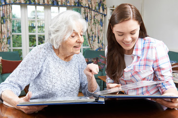 Grandmother Looking At Photo Album With Teenage Granddaughter