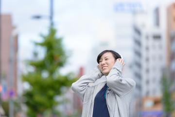 音楽を聞きながら街を歩く女性