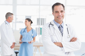 Doctor looking at camera while his colleagues works
