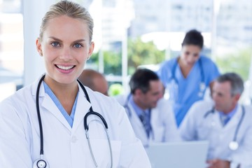 Smiling female doctor looking at camera while her colleagues wor