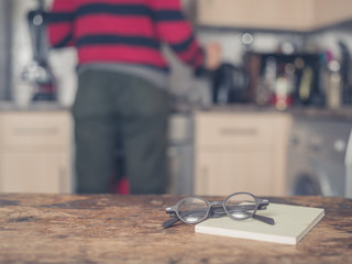 Book and glasses on table in kitchen