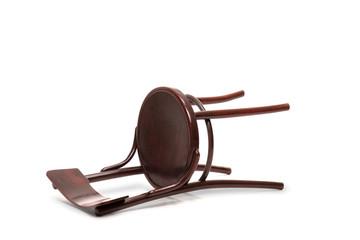 Brown wooden chair fallen down on the floor