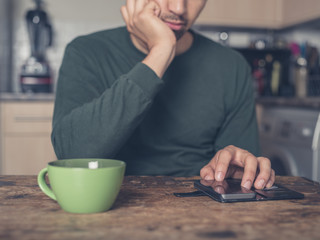 Young man drinking coffee and using smart phone