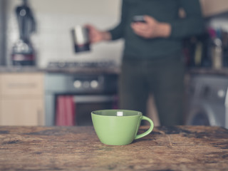 Cup of coffee in kitchen with man in background