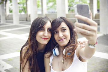 Two beautiful girls taking a selfie outdoor