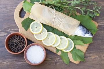 Fresh mackerel on paper in grape leaves with lemon slices