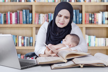 Woman with baby reading books in library