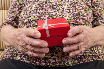 close up hands of a senior woman holding a gift box