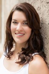 Junge attraktive Frau mit dunklen Haaren im Portrait lachend