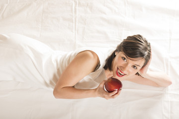Beautiful young woman posing with an red apple, studio shot on white