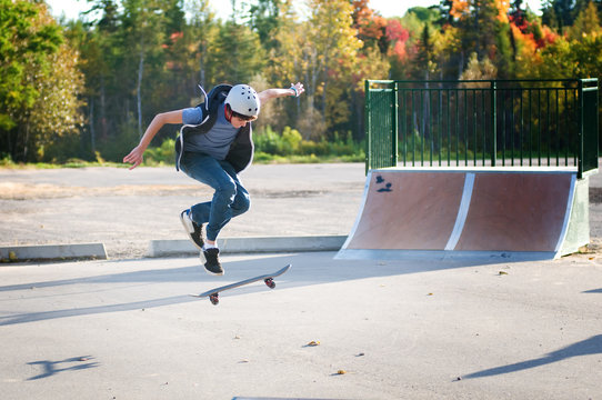 teen boy skateboarding at the local skate park on a beautiful fall evening