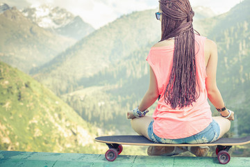 Hipster fashion girl doing yoga, relaxing on skateboard at mountain