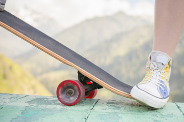 teenager doing a trick by skateboard outdoor at mountain
