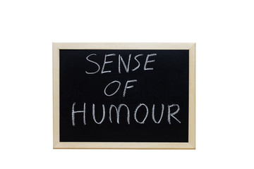 SENSE OF HUMOUR written with white chalk on blackboard.