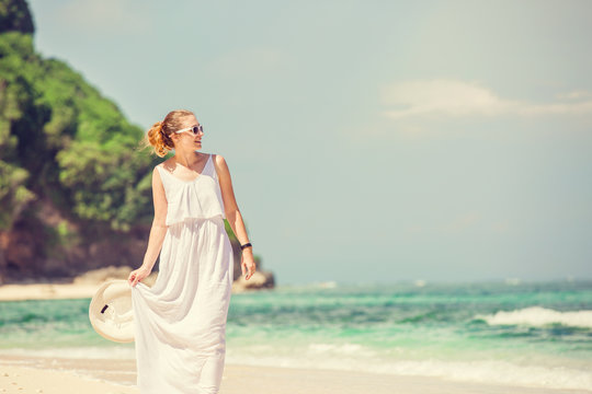 Young woman in long white dress holding hat walks along tropical beach having great summer time on holidays