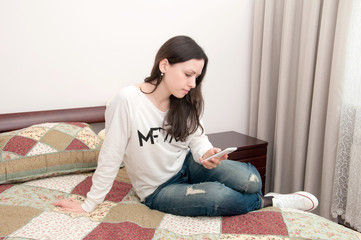 Young girl sitting on the bed and playing with a mobile phone