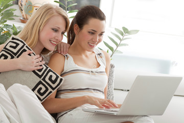 Two Young Beautiful Women Surfing the Net at Home
