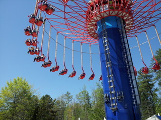 Aerial swing ride  at theme park with trees