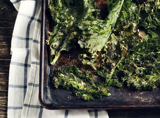 Crispy cheese and chili kale chips on baking tray. Toned image