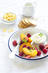 fresh peaches and raspberries in an enamel plate on a light background