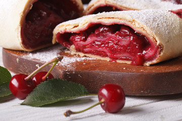 Slice of homemade cherry strudel close-up on a wooden board