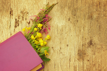 Spring bouquet of flowers and the book on a wooden surface