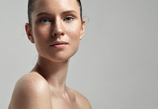 freckles woman's face portrait with healthy skin..