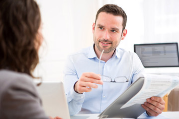Young attractive employer analysing resume of woman