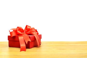 Red gift box and ribbon on wooden table