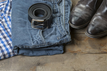 Jeans, Leather Boots, shirt and Belt on wooden Background
